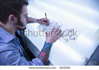 stock photo : Caucasian male tattoo artist drawing tattoo on light